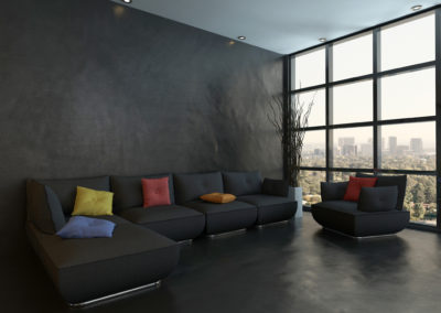 Black couch with colorful pillows against wooden wall